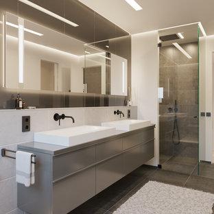 Mittelgroßes Modernes Duschbad mit flächenbündigen Schrankfronten, grauen Schränken, Eckdusche, grauen Fliesen, Porzellanfliesen, beiger Wandfarbe, Porzellan-Bodenfliesen, Aufsatzwaschbecken, grauem Boden, Falttür-Duschabtrennung und grauer Waschtischplatte in Düsseldorf