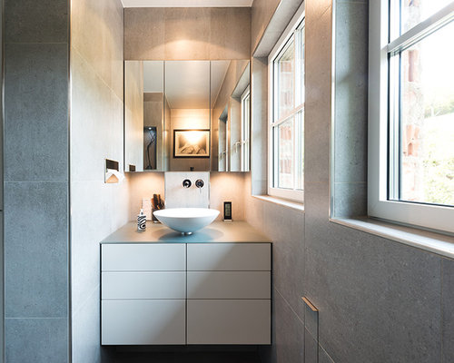 Modernes Badezimmer Mit Flächenbündigen Schrankfronten, Weißen Schränken, Grauen  Fliesen, Aufsatzwaschbecken Und Steinfliesen In