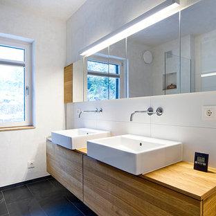 Modernes Badezimmer Mit Flächenbündigen Schrankfronten, Hellbraunen  Holzschränken, Weißer Wandfarbe, Aufsatzwaschbecken Und Weißen Fliesen