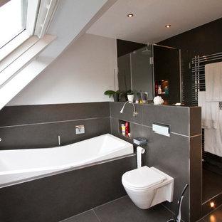 Modelo de cuarto de baño actual, pequeño, con paredes blancas, ducha empotrada, baldosas y/o azulejos negros, bañera empotrada y sanitario de pared