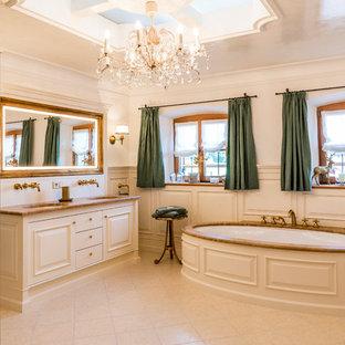 Badezimmer mit profilierten Schrankfronten, weißen Schränken, freistehender Badewanne, weißer Wandfarbe, Unterbauwaschbecken, beigem Boden, Falttür-Duschabtrennung und brauner Waschtischplatte in München