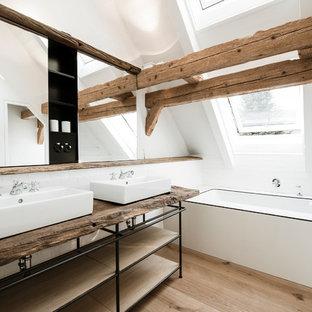 Modelo de cuarto de baño escandinavo, de tamaño medio, con baldosas y/o azulejos blancos, baldosas y/o azulejos de cemento, paredes blancas, suelo de madera en tonos medios, encimera de madera, bañera encastrada sin remate y encimeras marrones