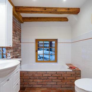 Diseño de cuarto de baño rústico, pequeño, con bañera encastrada, sanitario de pared, lavabo bajoencimera, suelo de baldosas de terracota, armarios con paneles con relieve, puertas de armario blancas, baldosas y/o azulejos blancos y paredes blancas