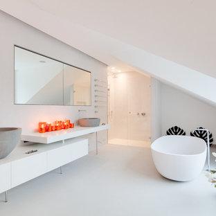 Großes Modernes Badezimmer mit flächenbündigen Schrankfronten, weißen Schränken, freistehender Badewanne, bodengleicher Dusche, weißer Wandfarbe, Betonboden, Aufsatzwaschbecken, Beton-Waschbecken/Waschtisch und Falttür-Duschabtrennung in München