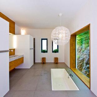 Mittelgroßes Modernes Badezimmer mit weißer Wandfarbe, grauem Boden, flächenbündigen Schrankfronten, braunen Schränken, Einbaubadewanne, Aufsatzwaschbecken und Waschtisch aus Holz in Sonstige