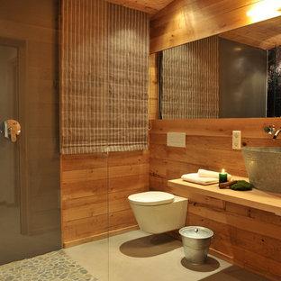 他の地域の中サイズのラスティックスタイルのおしゃれなバスルーム (浴槽なし) (コーナー設置型シャワー、石タイル、ベッセル式洗面器、壁掛け式トイレ、木製洗面台、茶色い壁、オープンシャワー、ブラウンの洗面カウンター) の写真