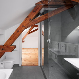 Large mountain style master gray tile and ceramic tile ceramic floor, gray floor, double-sink and exposed beam bathroom photo in Munich with a wall-mount toilet, white walls and a wall-mount sink