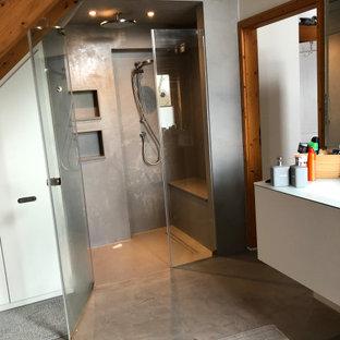Exempel på ett mellanstort modernt vit vitt badrum med dusch, med släta luckor, grå skåp, en kantlös dusch, en toalettstol med separat cisternkåpa, grå kakel, stenhäll, vita väggar, betonggolv, ett nedsänkt handfat, bänkskiva i glas, grått golv och dusch med gångjärnsdörr