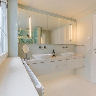 Mittelgroßes Modernes Duschbad mit blauen Fliesen, Keramikfliesen, beiger Wandfarbe, Keramikboden, Wandwaschbecken, beigem Boden, weißer Waschtischplatte, flächenbündigen Schrankfronten und weißen Schränken in München