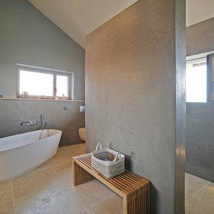 Mittelgroßes Modernes Badezimmer En Suite mit freistehender Badewanne, bodengleicher Dusche, grauer Wandfarbe, Travertin, beigem Boden, offener Dusche und Wandtoilette mit Spülkasten in München