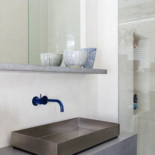 Großes Modernes Badezimmer En Suite mit flächenbündigen Schrankfronten, weißen Schränken, freistehender Badewanne, weißer Wandfarbe, Aufsatzwaschbecken, Edelstahl-Waschbecken/Waschtisch, beigem Boden und grauer Waschtischplatte in London