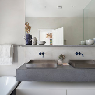 Inspiration for a large contemporary ensuite bathroom in London with flat-panel cabinets, white cabinets, a freestanding bath, blue tiles, white tiles, ceramic tiles, white walls, a vessel sink, grey worktops, a corner shower, concrete worktops and a hinged door.