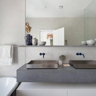 Großes Modernes Badezimmer En Suite mit flächenbündigen Schrankfronten, weißen Schränken, freistehender Badewanne, blauen Fliesen, weißen Fliesen, Keramikfliesen, weißer Wandfarbe, Aufsatzwaschbecken, grauer Waschtischplatte, Eckdusche, Beton-Waschbecken/Waschtisch und Falttür-Duschabtrennung in London