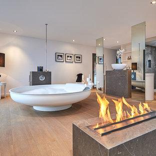 Foto de cuarto de baño principal, actual, extra grande, con bañera exenta, paredes blancas, suelo de madera en tonos medios, lavabo sobreencimera y suelo marrón