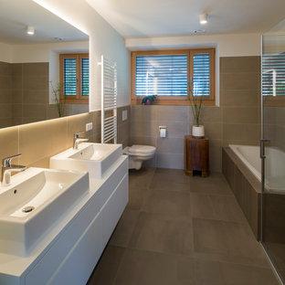 Ispirazione per una stanza da bagno padronale minimalista con ante lisce, vasca da incasso, doccia ad angolo, WC sospeso, piastrelle beige, pareti bianche, lavabo a bacinella, pavimento beige, porta doccia a battente e top bianco