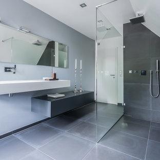 Imagen de cuarto de baño moderno, grande, con armarios con paneles lisos, puertas de armario grises, ducha a ras de suelo, baldosas y/o azulejos grises, paredes grises, lavabo suspendido y ducha abierta