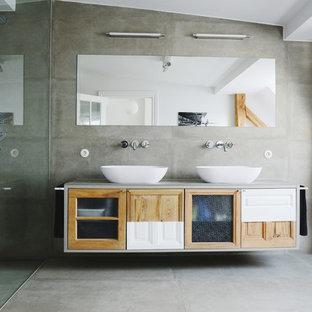 Foto de cuarto de baño actual, extra grande, con ducha a ras de suelo, baldosas y/o azulejos grises, paredes grises, suelo de cemento, lavabo sobreencimera, encimera de cemento y puertas de armario de madera oscura
