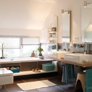 Mittelgroßes Modernes Badezimmer mit Einbaubadewanne, Wandtoilette, schwarzen Fliesen, weißer Wandfarbe, Aufsatzwaschbecken und Waschtisch aus Holz in Hamburg