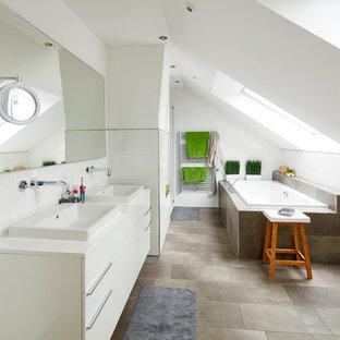 Großes Nordisches Duschbad mit flächenbündigen Schrankfronten, weißen Schränken, Einbaubadewanne, braunen Fliesen, weißen Fliesen, Einbauwaschbecken, grauem Boden und weißer Waschtischplatte in Bremen