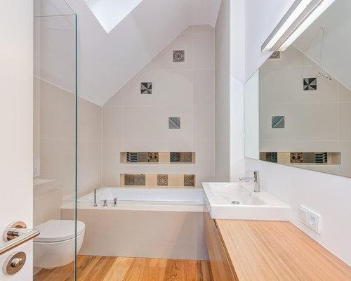 Kleines Modernes Badezimmer Mit Flächenbündigen Schrankfronten, Hellbraunen  Holzschränken, Badewanne In Nische, Wandtoilette,