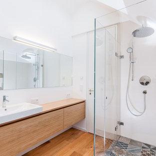 Стильный дизайн: ванная комната среднего размера в современном стиле с плоскими фасадами, фасадами цвета дерева среднего тона, угловым душем, разноцветной плиткой, белыми стенами, столешницей из дерева, керамической плиткой, паркетным полом среднего тона и настольной раковиной - последний тренд