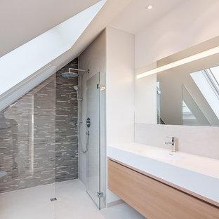 Mittelgroßes Modernes Duschbad mit bodengleicher Dusche, grauen Fliesen, Mosaikfliesen, integriertem Waschbecken, flächenbündigen Schrankfronten, hellbraunen Holzschränken, Waschtisch aus Holz, weißer Wandfarbe und brauner Waschtischplatte in München