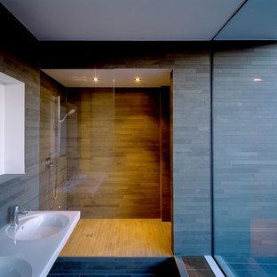 Réalisation d'une grand douche en alcôve minimaliste avec un lavabo intégré, un carrelage gris, des carreaux en allumettes, un mur gris et un sol en ardoise.