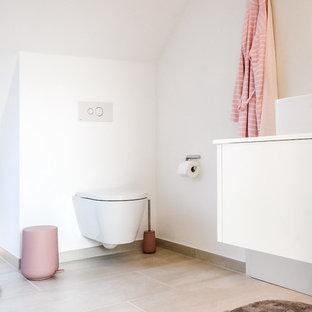 Mittelgroßes Modernes Duschbad mit Wandtoilette mit Spülkasten, Aufsatzwaschbecken, flächenbündigen Schrankfronten, weißen Schränken, weißen Fliesen, weißer Wandfarbe, Kalkstein, beigem Boden und weißer Waschtischplatte in Dortmund