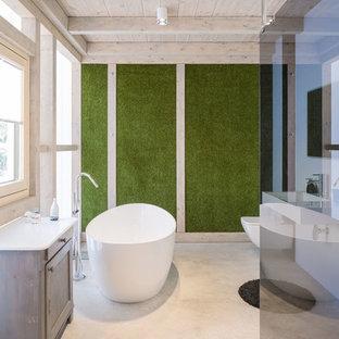 Großes Modernes Badezimmer En Suite mit bodengleicher Dusche, Wandtoilette, grüner Wandfarbe, Betonboden, Wandwaschbecken, offener Dusche, profilierten Schrankfronten, hellen Holzschränken, freistehender Badewanne und grauem Boden in Sonstige