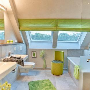 Großes Modernes Badezimmer En Suite mit Einbaubadewanne, Wandtoilette, grauen Fliesen, beiger Wandfarbe, Porzellan-Bodenfliesen, Wandwaschbecken, grauem Boden und offener Dusche in Hamburg