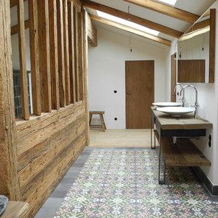 Ejemplo de cuarto de baño campestre, grande, con lavabo sobreencimera, armarios abiertos, paredes blancas, encimera de madera y encimeras marrones
