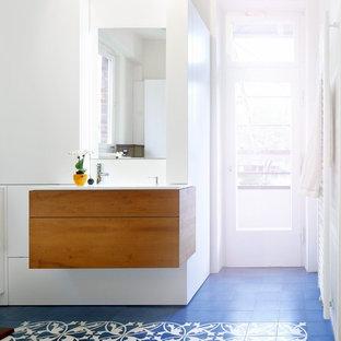 Cette image montre une grand salle de bain principale design avec un placard à porte plane, des portes de placard oranges, une baignoire en alcôve, un espace douche bain, un bidet, un sol en carrelage de terre cuite, un lavabo intégré, un plan de toilette en surface solide, un sol bleu et un plan de toilette blanc.