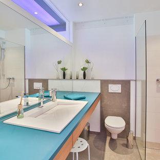Kleines Industrial Duschbad mit flächenbündigen Schrankfronten, hellen Holzschränken, braunen Fliesen, weißer Wandfarbe, Einbauwaschbecken, beigem Boden, offener Dusche, blauer Waschtischplatte, Eckdusche und Wandtoilette in Köln