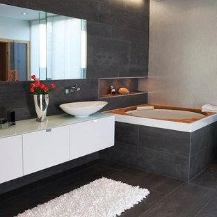 ニュルンベルクの大きいコンテンポラリースタイルのおしゃれなマスターバスルーム (ベッセル式洗面器、フラットパネル扉のキャビネット、白いキャビネット、和式浴槽、グレーのタイル、グレーの壁、石スラブタイル、スレートの床、ガラスの洗面台) の写真