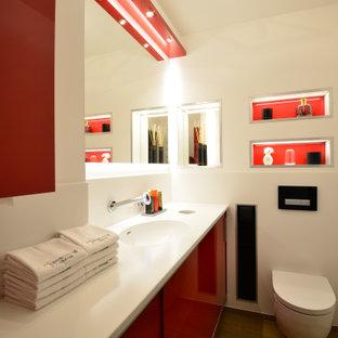 Mittelgroßes Modernes Duschbad mit flächenbündigen Schrankfronten, roten Schränken, Wandtoilette, weißen Fliesen, Porzellanfliesen, weißer Wandfarbe, integriertem Waschbecken und weißer Waschtischplatte in Hannover