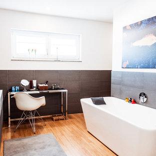 Diseño de cuarto de baño principal, contemporáneo, extra grande, con armarios abiertos, bañera exenta, ducha a ras de suelo, baldosas y/o azulejos grises, baldosas y/o azulejos de cerámica, paredes blancas, suelo de bambú y lavabo sobreencimera