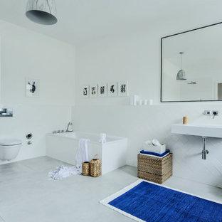 Mittelgroßes Modernes Duschbad mit Einbaubadewanne, Duschbadewanne, Wandtoilette, weißen Fliesen, Keramikfliesen, weißer Wandfarbe, Zementfliesen, Wandwaschbecken, Mineralwerkstoff-Waschtisch und grauem Boden in Düsseldorf