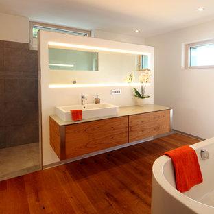 Mittelgroßes Modernes Badezimmer En Suite mit flächenbündigen Schrankfronten, hellbraunen Holzschränken, freistehender Badewanne, braunen Fliesen, weißer Wandfarbe, braunem Holzboden, Aufsatzwaschbecken, braunem Boden und beiger Waschtischplatte in München