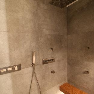Foto de cuarto de baño con ducha, urbano, grande, con puertas de armario de madera en tonos medios, ducha a ras de suelo, sanitario de pared, baldosas y/o azulejos grises, baldosas y/o azulejos de terracota, paredes blancas, suelo de baldosas de cerámica, lavabo integrado, encimera de azulejos, suelo gris y encimeras grises