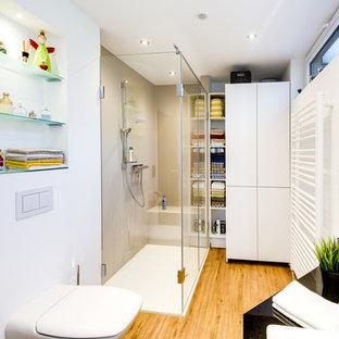 Cette photo montre une salle d'eau tendance de taille moyenne avec un placard à porte plane, des portes de placard blanches, une douche à l'italienne, un WC suspendu, un carrelage blanc, des carreaux de céramique, un mur blanc, un sol en bois peint, une vasque, un plan de toilette en surface solide, un sol marron, une cabine de douche à porte coulissante et un plan de toilette blanc.