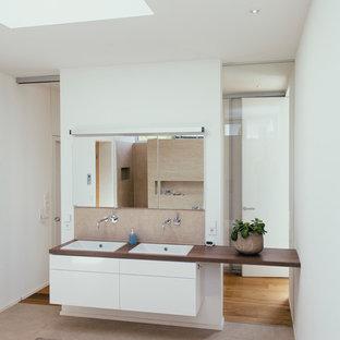 Mittelgroßes Modernes Badezimmer Mit Flächenbündigen Schrankfronten, Weißen  Schränken, Beigefarbenen Fliesen, Weißer Wandfarbe,