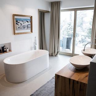 Mittelgroßes Modernes Badezimmer En Suite mit freistehender Badewanne, weißer Wandfarbe, Betonboden, Aufsatzwaschbecken, Waschtisch aus Holz, grauem Boden und brauner Waschtischplatte in München