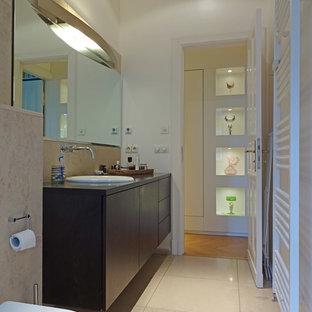Foto de cuarto de baño principal, minimalista, de tamaño medio, con armarios tipo vitrina, puertas de armario marrones, bañera japonesa, baldosas y/o azulejos beige, baldosas y/o azulejos de travertino, suelo de travertino, encimera de acrílico y encimeras marrones