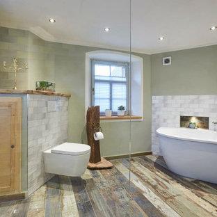 Imagen de cuarto de baño principal, rústico, grande, con bañera exenta, ducha abierta, sanitario de pared, baldosas y/o azulejos grises, paredes verdes, suelo de madera pintada, suelo multicolor y ducha abierta