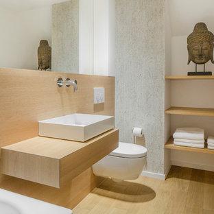 Modernes Badezimmer mit offenen Schränken, hellbraunen Holzschränken, Einbaubadewanne, Wandtoilette, weißer Wandfarbe, hellem Holzboden, Aufsatzwaschbecken, Waschtisch aus Holz, braunem Boden und brauner Waschtischplatte in Düsseldorf