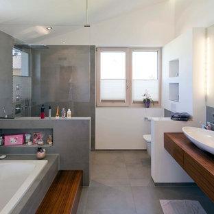 Modern inredning av ett stort brun brunt badrum med dusch, med släta luckor, skåp i mellenmörkt trä, ett platsbyggt badkar, en öppen dusch, en vägghängd toalettstol, grå kakel, cementkakel, vita väggar, cementgolv, ett fristående handfat, träbänkskiva, grått golv och med dusch som är öppen
