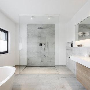 На фото: главная ванная комната в стиле модернизм с плоскими фасадами, отдельно стоящей ванной, душем без бортиков, серой плиткой, белыми стенами, фасадами цвета дерева среднего тона, бетонным полом, настольной раковиной и открытым душем с