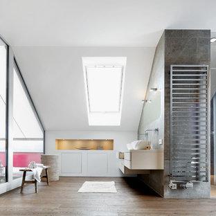 Modernes Badezimmer mit flächenbündigen Schrankfronten, weißen Schränken, Duschnische, grauen Fliesen, weißer Wandfarbe, braunem Holzboden, Aufsatzwaschbecken, braunem Boden, Falttür-Duschabtrennung und weißer Waschtischplatte in München
