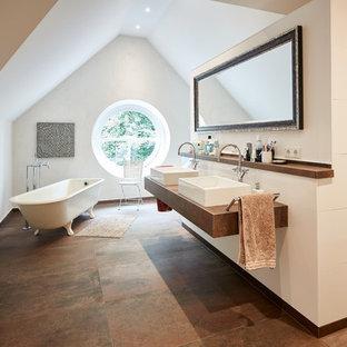 Imagen de cuarto de baño principal, campestre, grande, con bañera con patas, ducha abierta, baldosas y/o azulejos blancos, paredes blancas, lavabo sobreencimera, encimera de madera, suelo marrón, ducha abierta, encimeras marrones y sanitario de pared