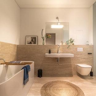 Ispirazione per una stanza da bagno con doccia design di medie dimensioni con vasca freestanding, WC sospeso, piastrelle beige, lastra di pietra, pavimento in pietra calcarea, lavabo sospeso, pavimento beige e pareti bianche